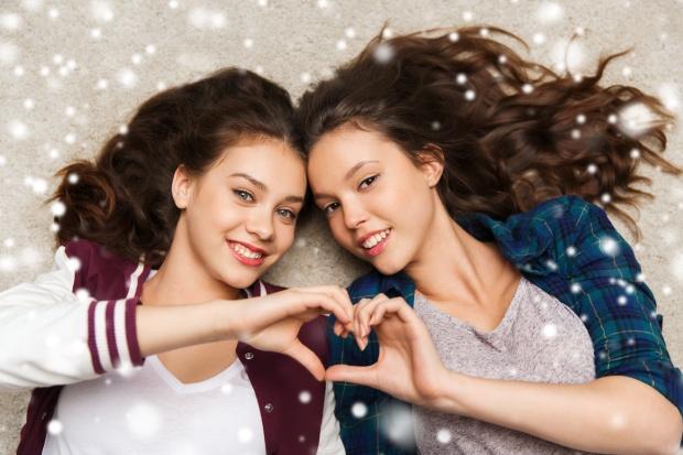 happy teenage girls lying on floor with heart